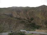 La carretera baja en zig-zag de vértigo, acompañando el perfil de las montañas.