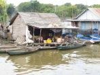 """Familia seleccionando el pescado. Véase el humo detrás de la casa. Aquí no pasa """"el barco de la basura"""", así que queman lo que les sobra en los """"patios traseros"""" y a la marcha."""