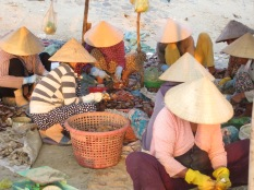 Mujeres en acción con sus típicos sombreros cónicos protegiéndoles de los últimos rayos de sol.