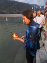 Karol arrojando al río su pequeña ofrenda de flores y llamas.